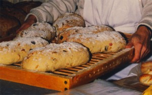 A tray of stollen, dusted with powdered sugar.